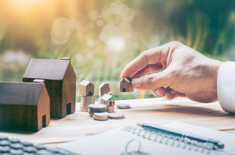 House placed on coins Men's hand is planning savings money of coins to buy a home concept concept for property ladder, mortgage and real estate investment. for saving or investment for a house,
