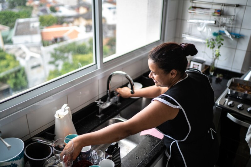 Housekeeper washing the dishes at house
