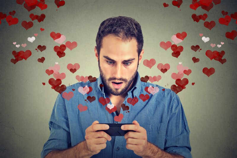 young handsome shocked man sending receiving love sms