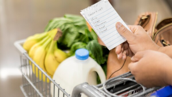 Unrecognizable woman checks items off grocery list