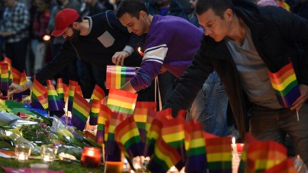 Un grupo de personas en Australia colocan objetos sobre una ofrenda en honor de las víctimas del tiroteo en Orlando.