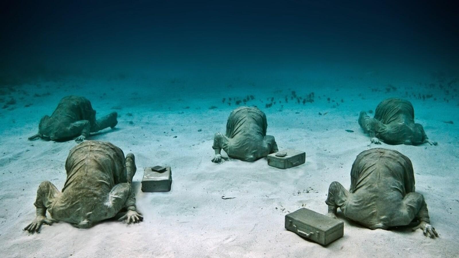 El artista no rehúye de una gran metáfora, como la instalación mostrada arriba en la que las figuras tienen las cabezas literalmente enterradas en la arena