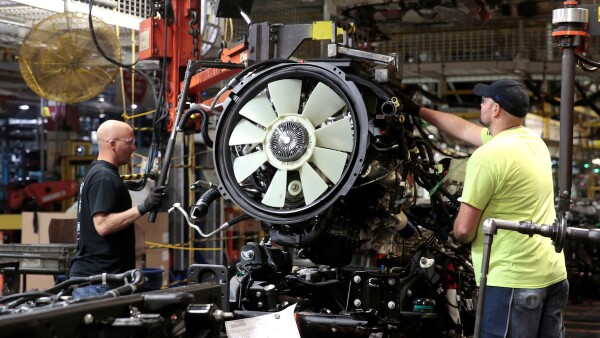 FILE PHOTO: General Motors assembly workers attach the engine to the chassis of Chevrolet 2019 heavy-duty pickup trucks at General Motors Flint Assembly Plant