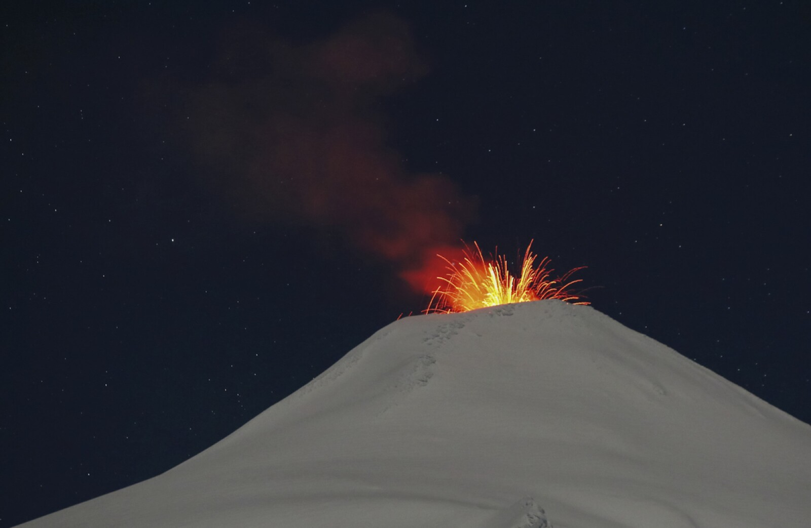 Villarrica volcano spews lava at night, seen from Pucon