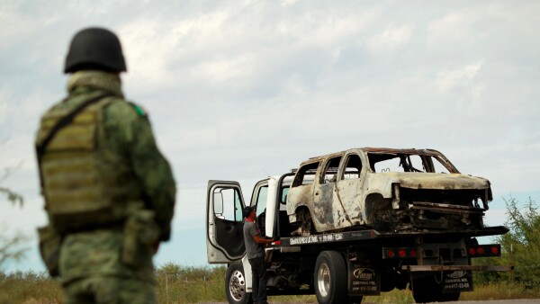 A soldier assigned to the National Guard keeps watches as a tow truck carrying the burnt wreckage of a truck, belonging to slain members of a Mexican-American Mormon family, is seen in Bavispe