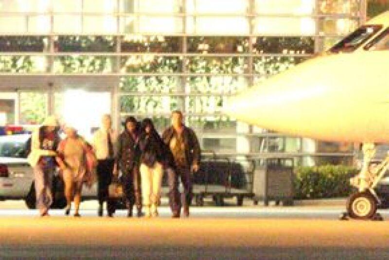 Rihanna (de pantalón blanco) viajó en el mismo avión que Chris Brown.