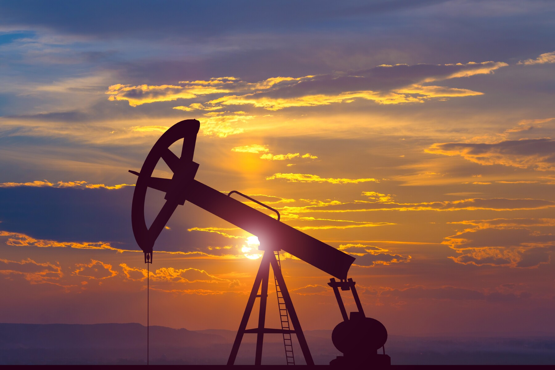 The oil pump on the background of the sunset