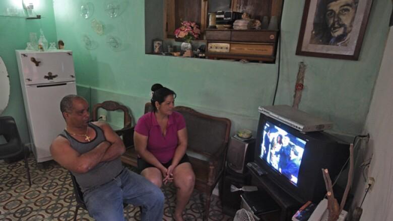 Una pareja de cubanos, acompañados por el retraro del Che Guevara, ven la transmisión de la televisión estatal