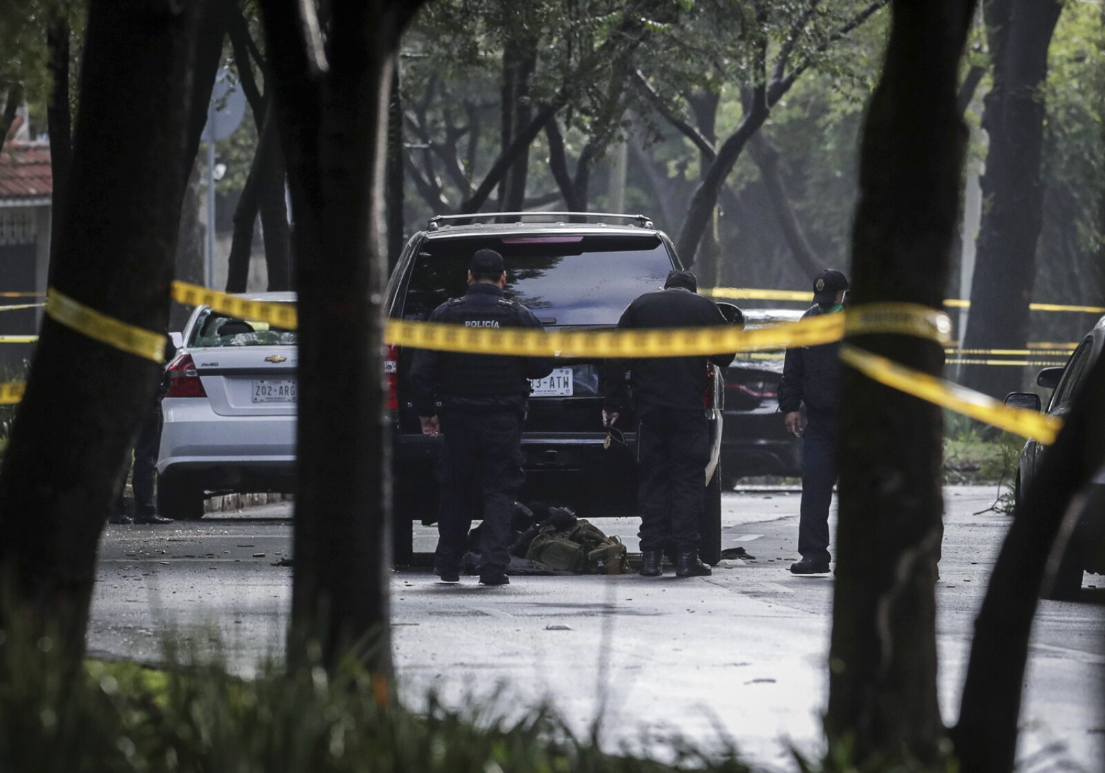 Police officers are seen near a vehicle after a shooting in Mexico City