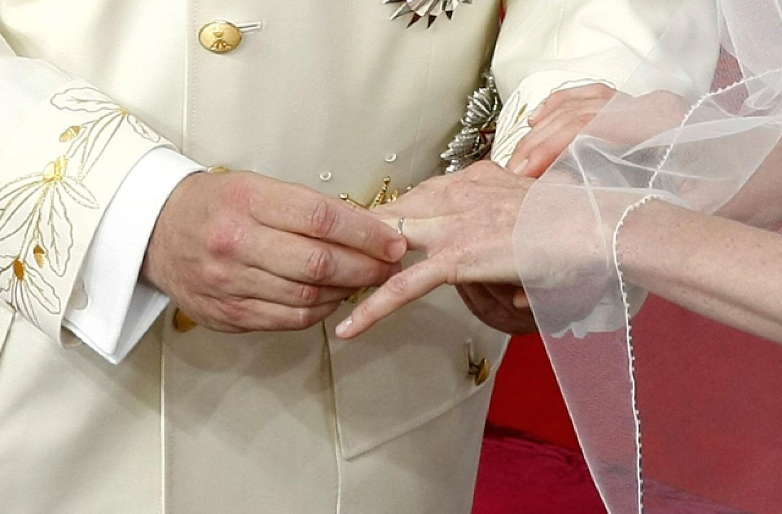Como muestra de amor y fidelidad, la pareja se coloca sus argollas de matrimonio.
