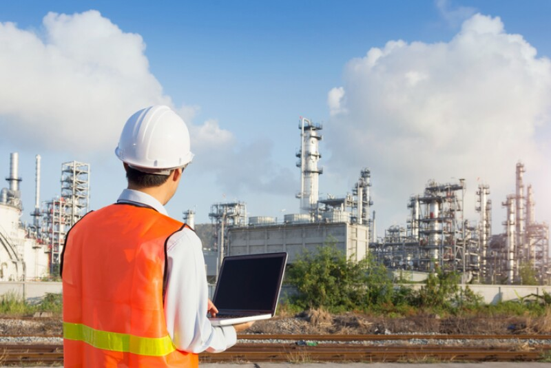 Maintenance engineer working with laptop in oil refinery