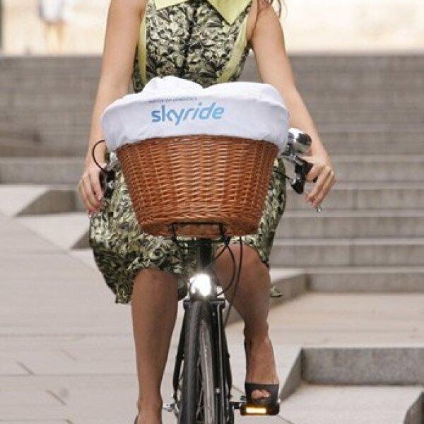 La guapísima Kelly Brook promocionó la campaña Skyride en Londres y se subió en bici sin importarle que traía vestido y tacones.
