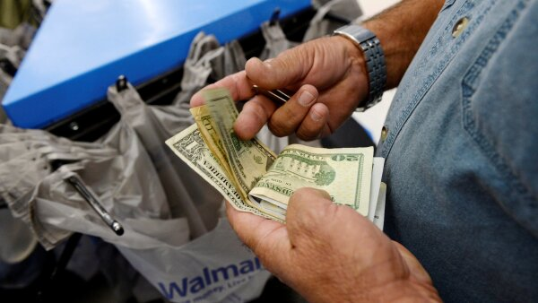 FILE PHOTO: A customer counts his cash at the checkout lane of a Walmart store in the Porter Ranch section of Los Angeles