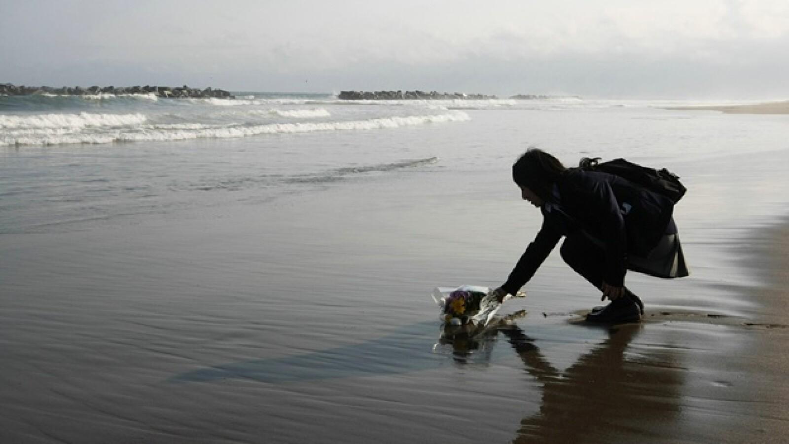Mai Otomo, joven de 17 años, deja flores ante el mar