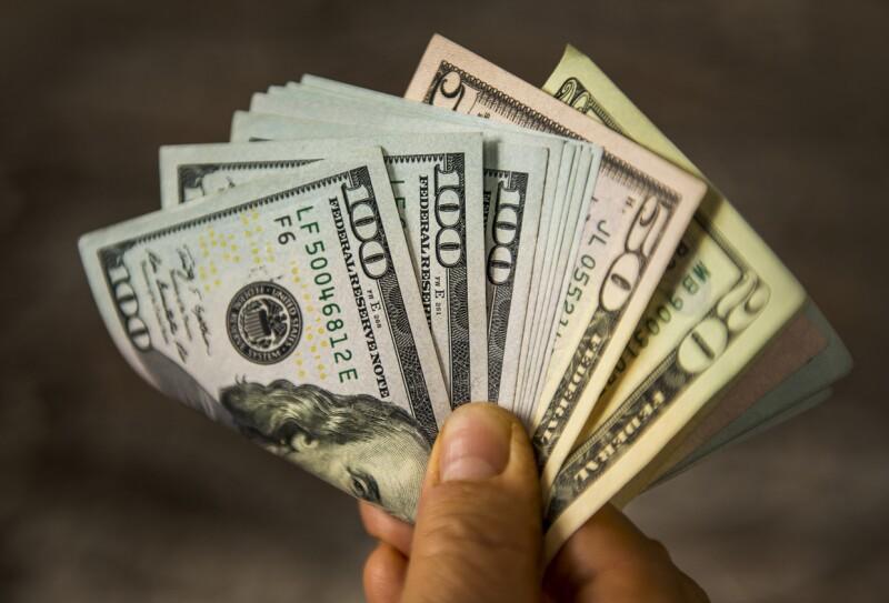 Unrecognizable mature man holding US Dollar bills