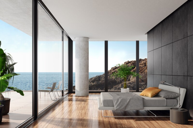 Modern luxurious bedroom in a seaside villa with black stone wall