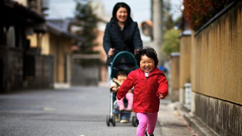 una madre asiatica pasea a sus hijos