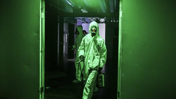 Los trabajadores que usan ropa protectora desinfectan un hotel como medida preventiva contra el coronavirus Covid-19 en Yangon el 25 de marzo de 2020, en Myanmar.