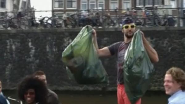 turistas recogen basura de los canales de Amsterdam