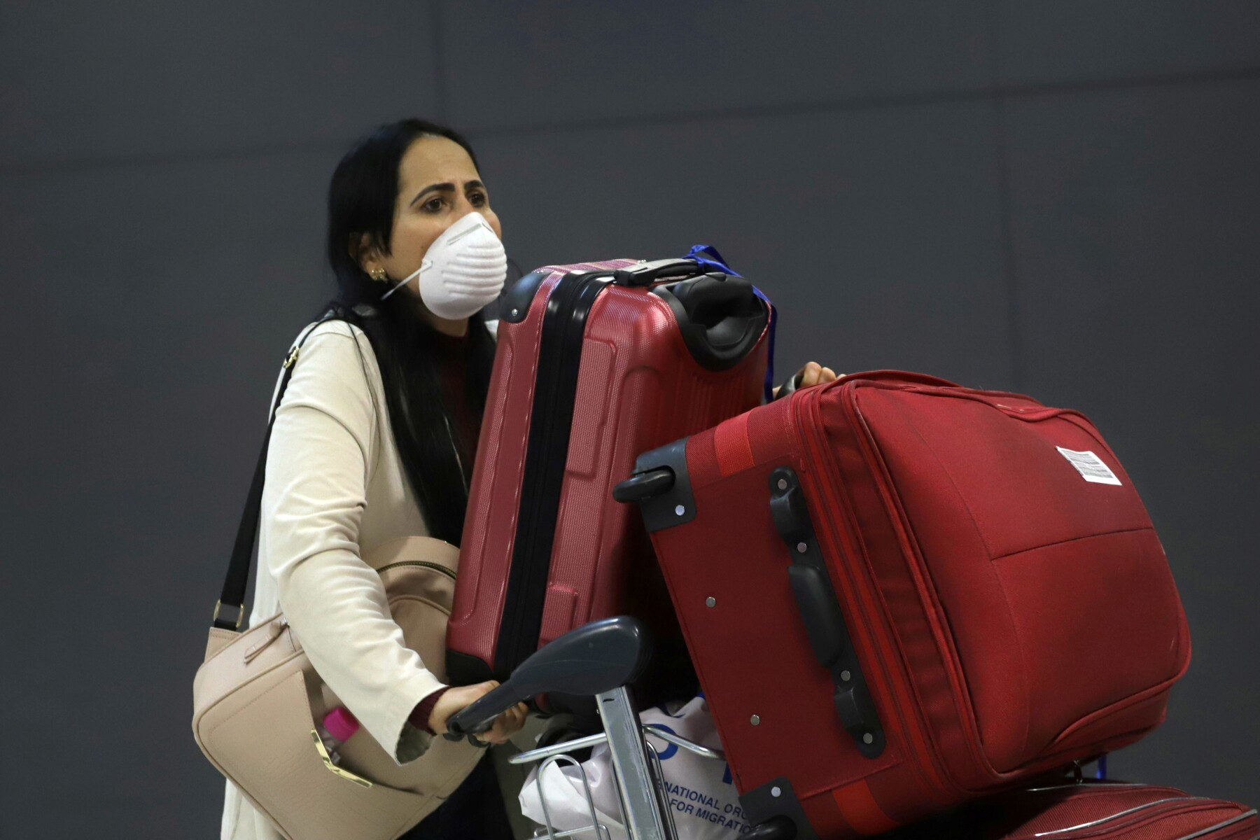 A woman wears a protective face mask at international arrivals area at Guarulhos International Airport in Guarulhos