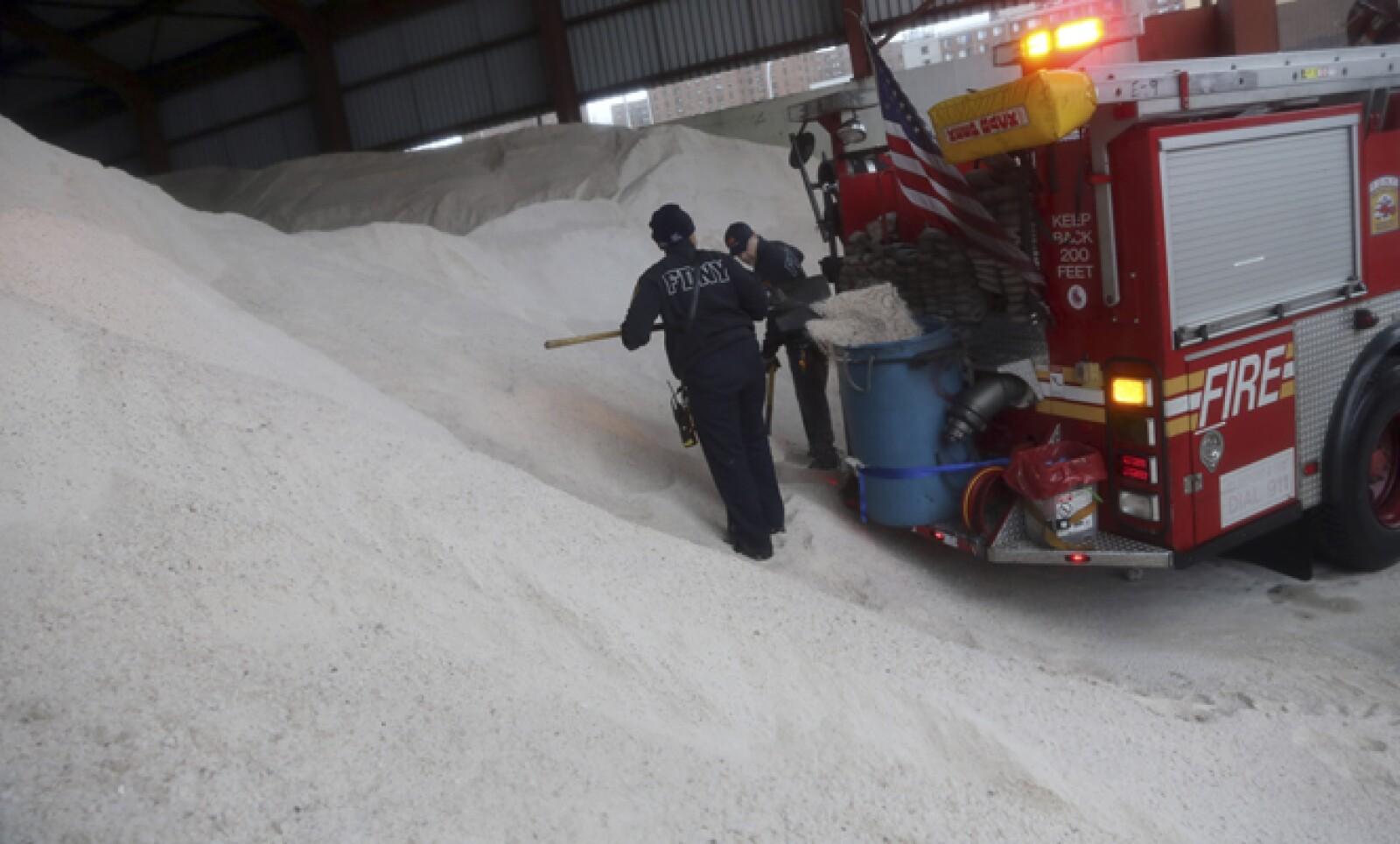 La acumulación de nieve fue muy rápida, lo que puede resultar peligroso. Bomberos de Nueva York cargan sal en un contenedor, misma que usan para derretir la nieve.