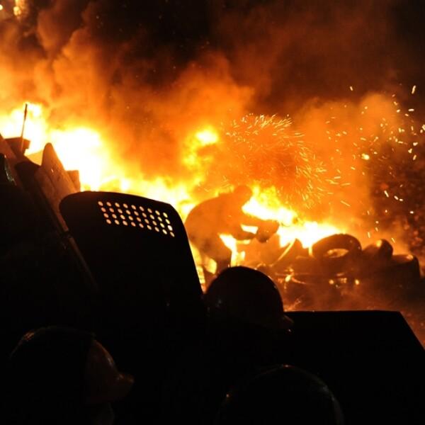 manifestante alimenta el fuego de una barricaad