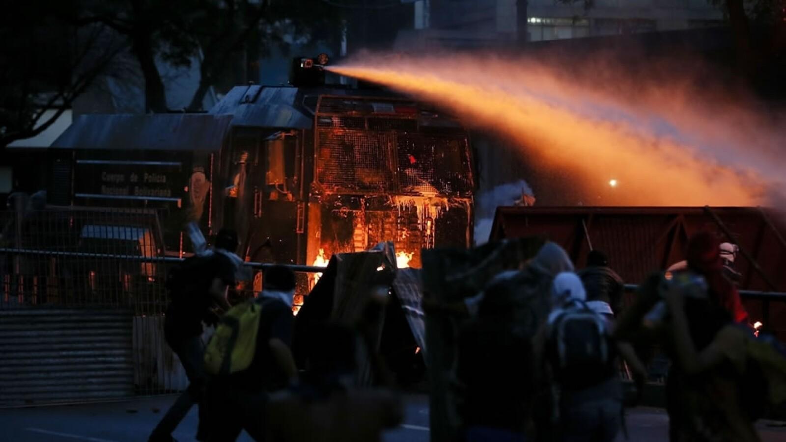 El vehículo gubernamental lanza chorros de agua los manifestantes de Caracas