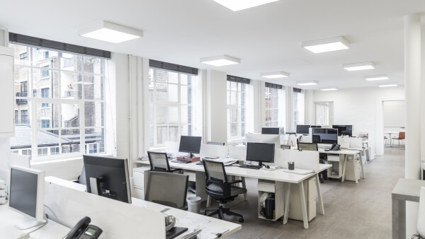 Large contemporary office environment with empty stations and electric ceiling lights