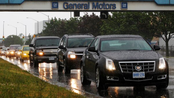 FILE PHOTO: A line up of cars is seen on a road after a shift change at the General Motors Car assembly plant in Oshawa