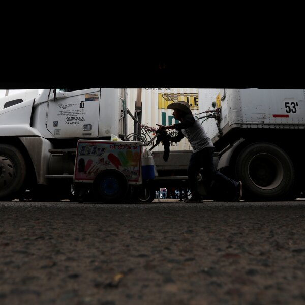 A man sells popsicles between trucks waiting in a long queue for border customs control to cross into the U.S., at the Otay border crossing in Tijuana