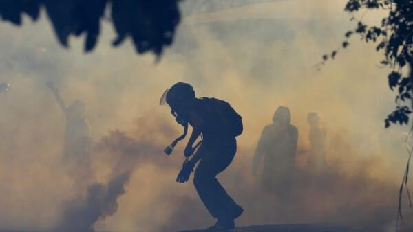 manifestante se cubre de gas lacrimógeno Caracas, Venezuela