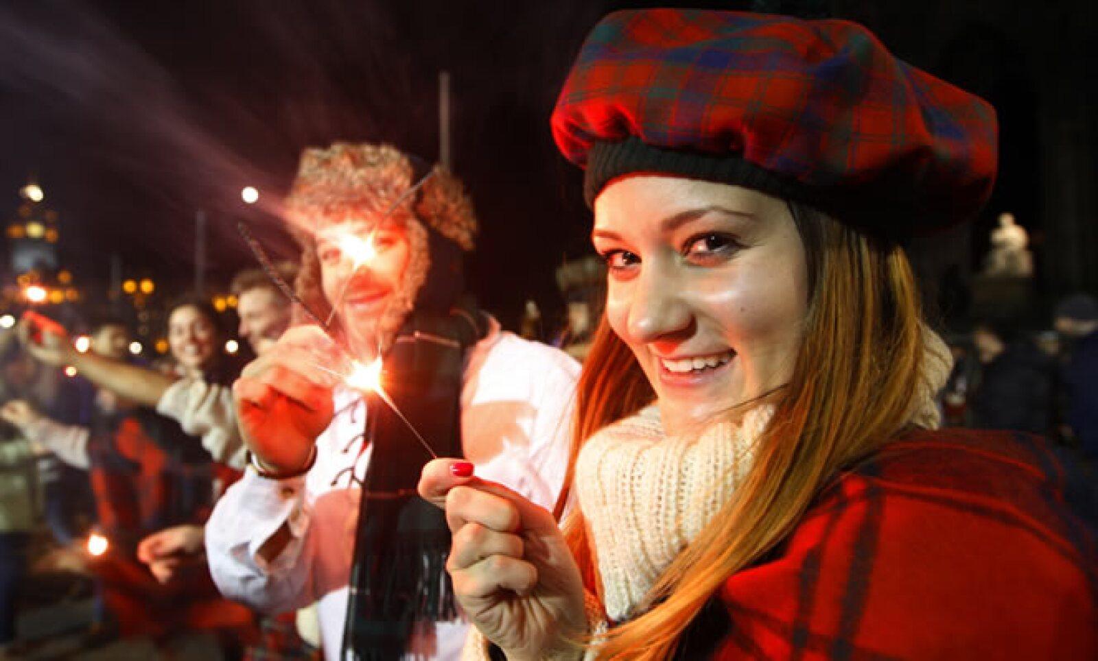 Una visitante de Austria sostiene una bengala durante la celebración en Edimburgo, Escocia.