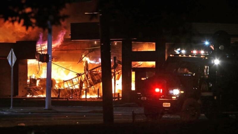 Una tienda de autoservicio fue incendiada durante una noche de saqueos en Ferguson, Missouri, tras la muerte de un joven negro