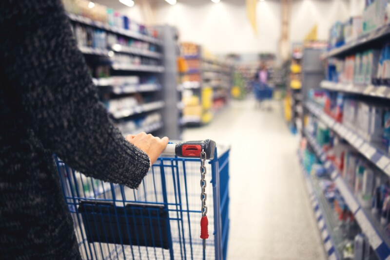 A women walks with a shopping basket in a store. Hand and part of the basket in focus