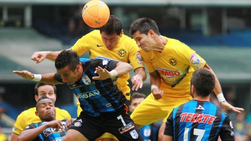 Los jugadores del América y Querétaro luchando por el esférico el sábado en el estadio Azteca