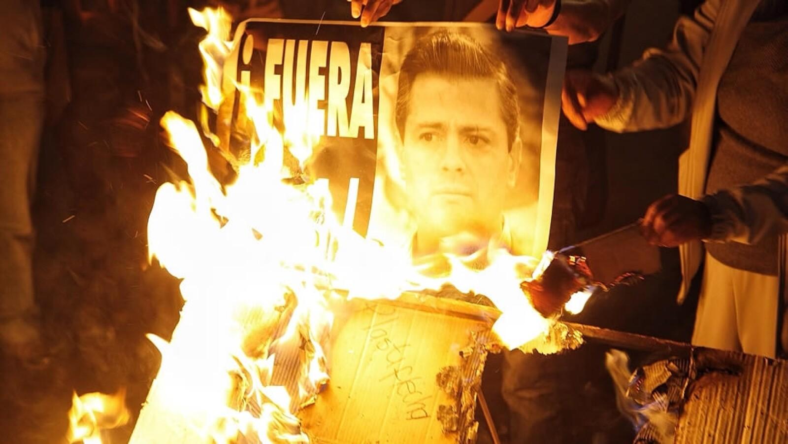 Un grupo de personas queman una fotografía del presidente Enrique Peña Nieto