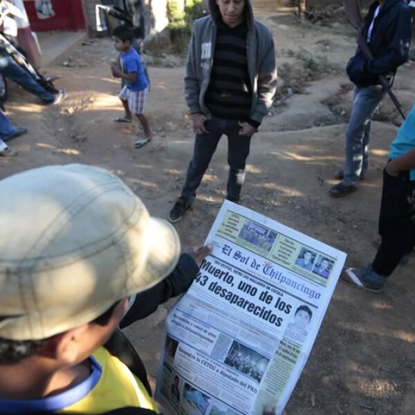 Un hombre lee un periódico local que da cuenta de la identificación de los restos del joven normalista