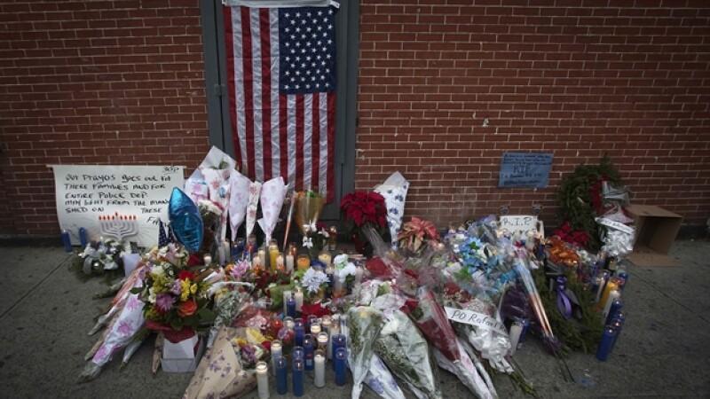 Flores, cartas y velas en un barrio de Brooklyn, donde fueron asesinados dos oficiales de policía el sábado