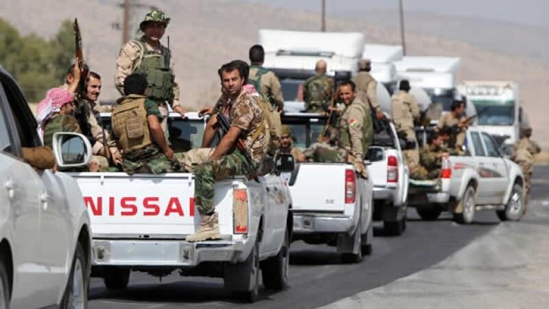 Combatientes kurdos se dirigente hacia Mosul, en el río Tigris, en la lucha por recuperar una presa en Iraq este domingo
