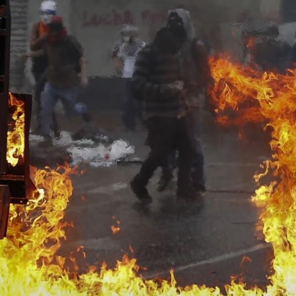 Un manifestante con una máscara de Guy Fawkes se enfrenta a fuerzas gubernamentales con un escudo en Caracas