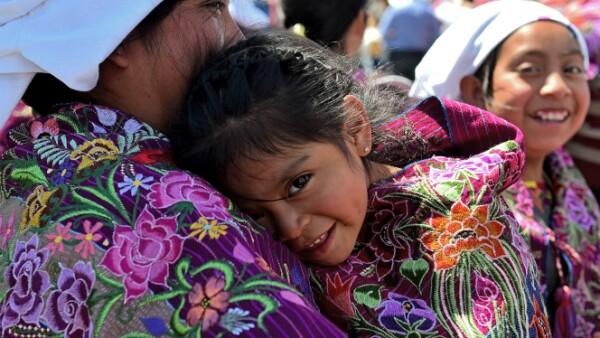 Una pequeña se refugia del sol en los brazos de su madre.