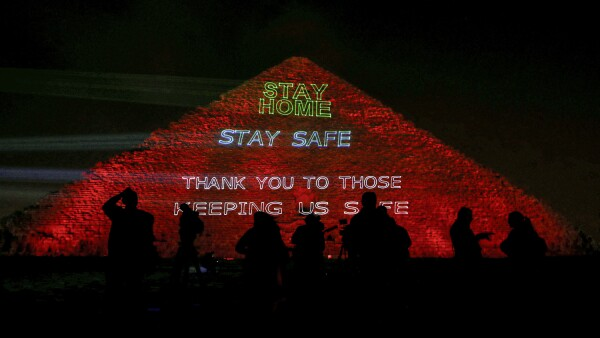 The pyramid of Khufu, the largest of the Giza pyramid complex, is illuminated with text encouraging to stay home, in Giza