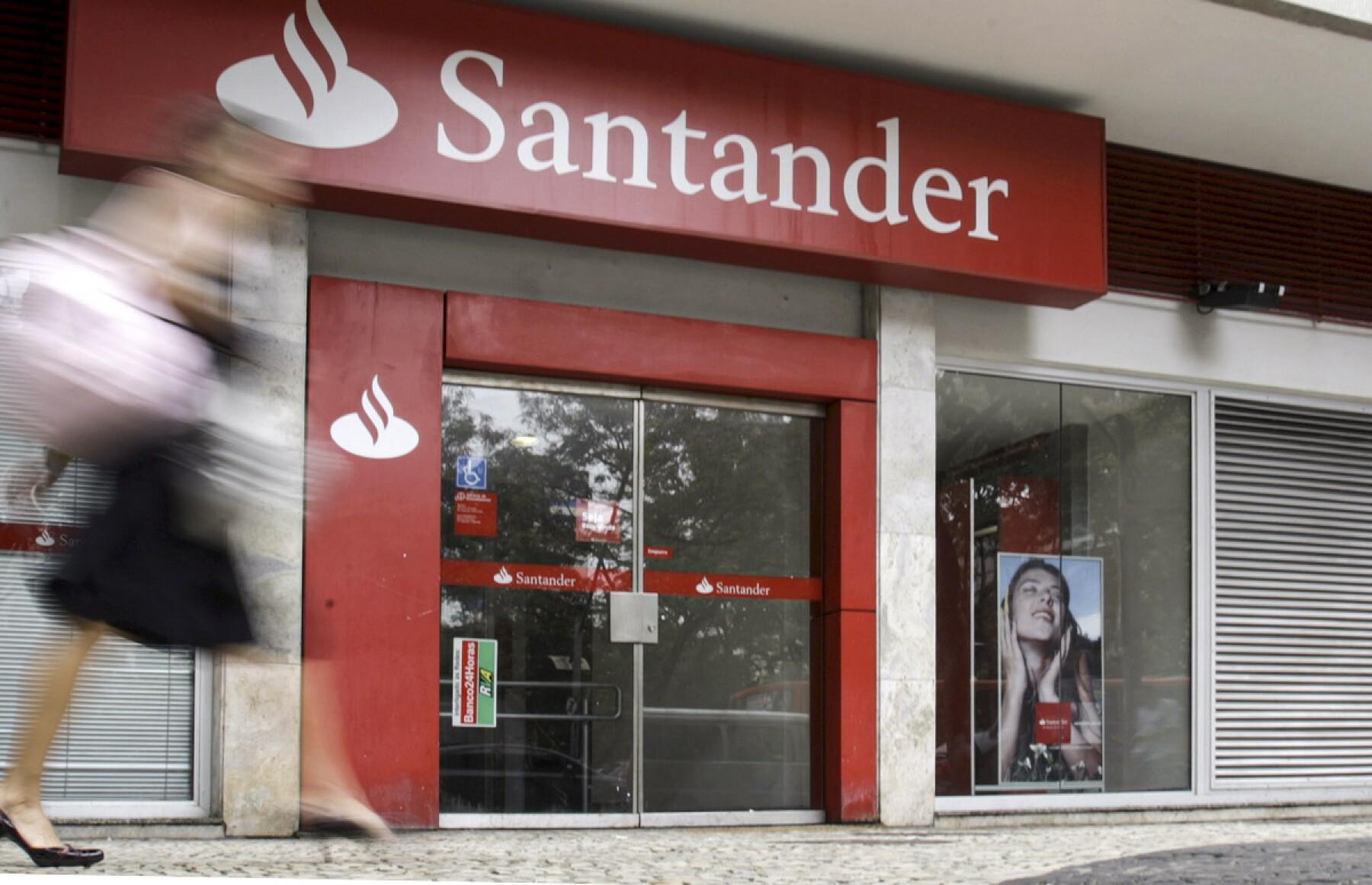 A woman walks past Santander bank branch in Rio de Janeiro