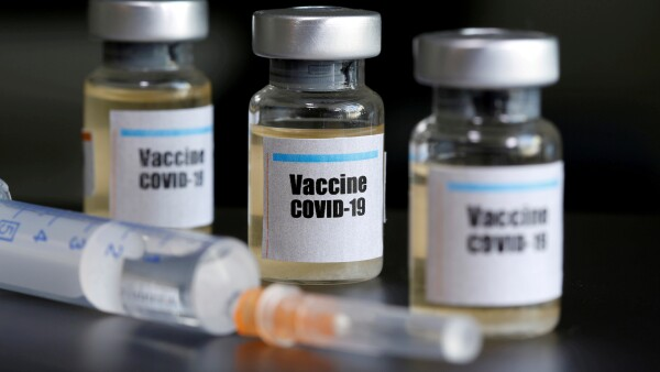 "FILE PHOTO: Small bottles labeled with a ""Vaccine COVID-19"" sticker and a medical syringe are seen in this illustration"
