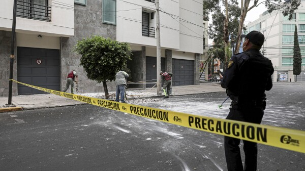 City workers remove debris from a building facade as a police officer checks, after an earthquake was felt in Mexico City