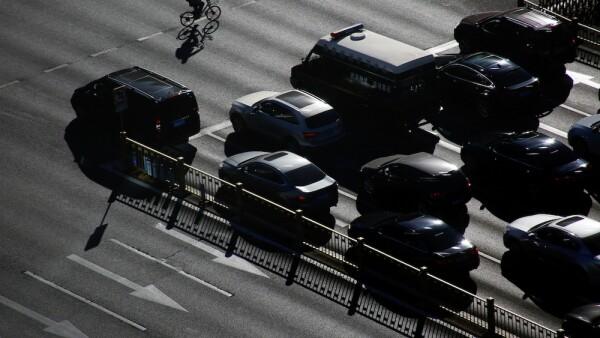 FILE PHOTO: A cyclist rides past cars that are waiting at a traffic light in central Beijing