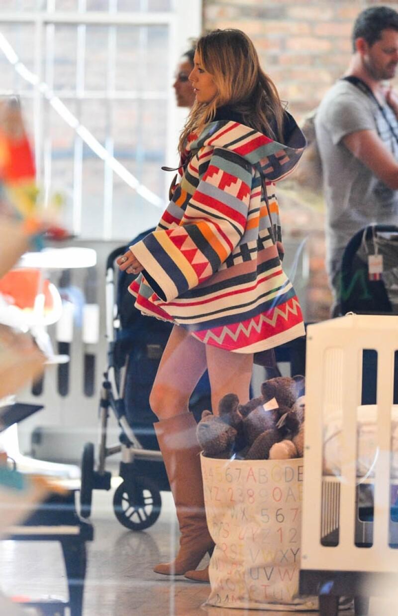 La guapa actriz que tiene más de cinco meses de embarazo cubrió su pancita en un colorido y original poncho mientras caminaba por las calles de la ciudad. Paró en la boutique &#39Giggle&#39 de bebés.