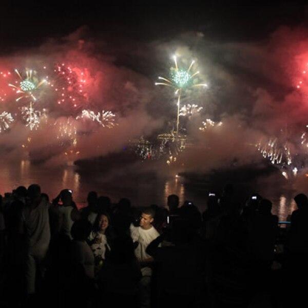 Fuegos artificiales explotan sobre la playa durante las celebraciones de Año Nuevo en Copacabana, Brasil.
