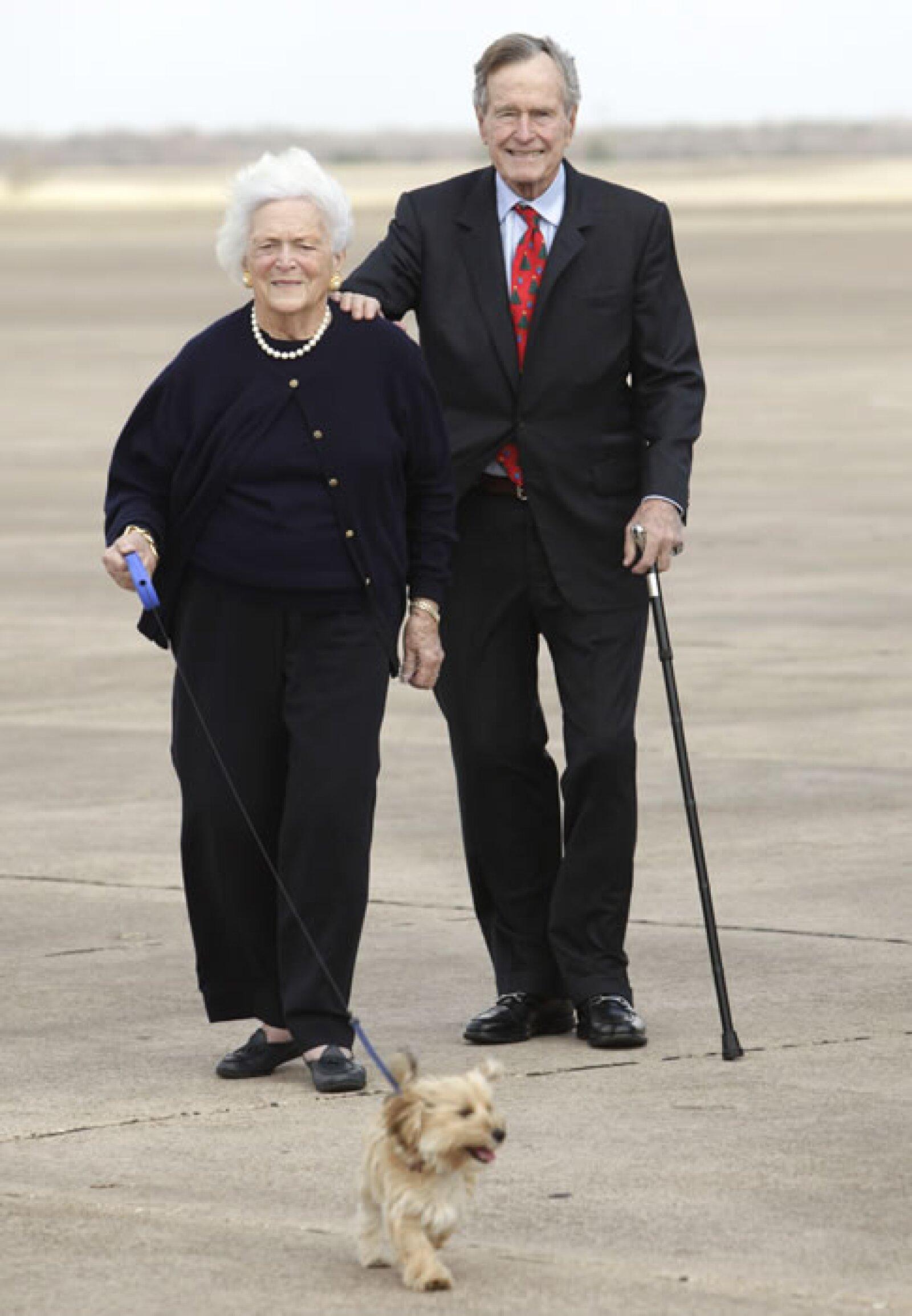 George y Barbara Bush sonríen mientras pasean a su perrito, quien seguramente es todo un consentido.