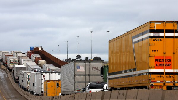Trucks wait in a long queue at border customs control to cross into the U.S, caused by the redeployment of border officers to deal with a surge in migrants, at the Otay border crossing in Tijuana